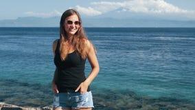 Красивый путешественник девушки в солнечных очках стоит около океана и представлений на камеру видеоматериал