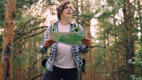 Красивый путешественник молодого человека идет в лес после этого стоя и смотря карта ища для правого пути после этого идя акции видеоматериалы