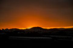 Красивый пылая ландшафт захода солнца на над небе луга и апельсина над им Изумительный восход солнца лета как предпосылка Стоковые Фото
