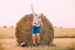 Красивый плюс девушка молодой женщины размера скача около стога сена Стоковые Фото