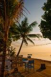 Красивый пляж с кафем в Sanur с местными традиционными пальмами шлюпок на острове Бали на зоре Индонезия Стоковое Фото