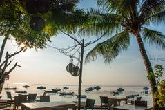 Красивый пляж с кафем в Sanur с местными традиционными пальмами шлюпок на острове Бали на зоре Индонезия Стоковая Фотография