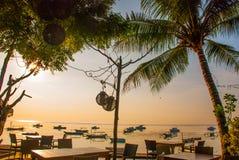 Красивый пляж с кафем в Sanur с местными традиционными пальмами шлюпок на острове Бали на зоре Индонезия Стоковое Изображение RF