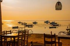 Красивый пляж с кафем в Sanur с местными традиционными шлюпками bali Индонесия рассвет Стоковые Изображения RF