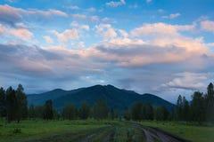 Красивый драматический заход солнца в горах Ландшафт при свет солнца светя через оранжевые облака Стоковые Фотографии RF
