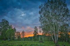 Красивый драматический заход солнца в горах Ландшафт при свет солнца светя через оранжевые облака Стоковая Фотография