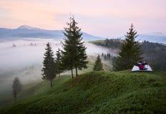 красивый рассвет в горах Силуэт девушки в туристском шатре на травянистом холме на туманной долине Стоковое Изображение RF