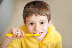 Красивый ребенк подготавливая почистить их зубы щеткой нося желтые купальные халаты closeup стоковое изображение rf