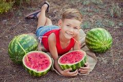 Красивый ребенок мальчика представляя в луге леса Central Park с арбузом лета свежим сочным красным зеленым с пластичной соломой  стоковая фотография