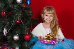 Красивый ребёнок в платье и в Новогодней ночи усмехаясь и ища подарок Стоковые Фото
