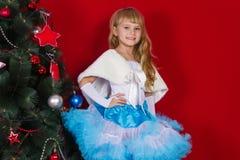 Красивый ребёнок в платье и в Новогодней ночи усмехаясь и ища подарок Стоковые Фотографии RF