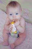 Красивый ребёнок сидя и всасывая на его игрушке Стоковое Фото
