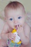 Красивый ребёнок сидя и всасывая на его игрушке Стоковое Изображение