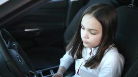 Красивый ребёнок смотря отсутствующий и усмехаясь пока сидящ в новом автомобиле в мотор-шоу акции видеоматериалы
