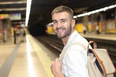 Красивый регулярный пассажир пригородных поездов усмехаясь пока ждущ его поезд стоковые фотографии rf