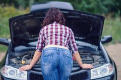 Красивый ремонтировать молодой женщины herbroken автомобиль около дороги, задний взгляд стоковые изображения rf