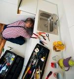 Красивый ремонт парня пускает по трубам на раковине в кухне Стоковое Изображение RF
