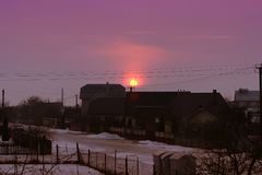 Красивый розовый заход солнца в деревне Ландшафт с заходом солнца и дома в деревне в зиме Стоковые Фотографии RF