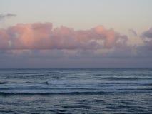 Красивый розовый и фиолетовый рассвет над океаном с свертывать волн Стоковая Фотография