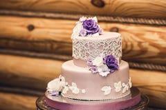 Красивый свадебный пирог в фиолетовых украшенных тонах, с шнурком и цветками стоковое изображение rf