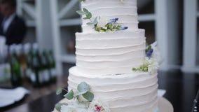 Красивый свадебный пирог показанный на таблице, как гости танцует на заднем плане видеоматериал