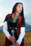 Красивый сексуальный ратник женщины с шпагой Предпосылка земли Стоковая Фотография RF