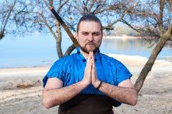 Красивый серьезный самурай в голубом кимоно, стоящ со сжиманными руками и шпагой за задней частью стоковые изображения rf