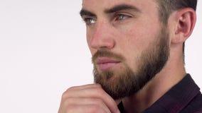 Красивый серьезный человек смотря прочь внимательно, трущ его бороду акции видеоматериалы