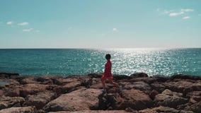 Красивый силуэт женщины идя на скалистую пристань моря самостоятельно Волны моря ударяя скалистый пляж Отражение дороги Солнца на акции видеоматериалы
