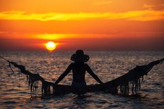 Красивый силуэт молодой женщины с качанием представляя в море на захо стоковая фотография rf