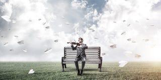 Красивый скрипач в парке на игре деревянной скамьи его мелодия Стоковые Изображения