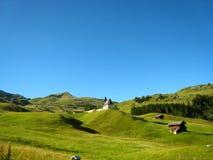 Красивый солнечный день с верхней частью горы голубого зеленого цвета и маленькими домами стоковые фото