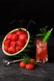 Красивый состав продуктов арбуза на черной предпосылке Красные ветроуловители арбуза и сладостный напиток ягоды Стоковое Изображение RF
