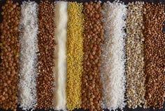 Красивый состав различных зерен на таблице: гречиха, пшено, манная крупа, чечевицы, ячмень жемчуга, рис стоковое фото rf