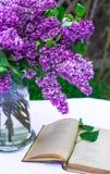 Красивый состав с старой книгой и букетом сирени в вазе на белой винтажной скатерти шнурка, серой предпосылке каменной стены Стоковое Изображение