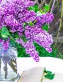 Красивый состав с старой книгой и букетом сирени в вазе на белой винтажной скатерти шнурка, серой предпосылке каменной стены Стоковые Фото