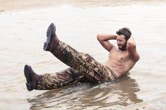 Красивый солдат делать завивает поднимает на морской воде стоковая фотография