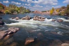 Красивый солнечный день осени на реке с водопадом и большим r Стоковые Изображения