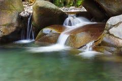 Красивый спокойный водопад среди утесов заводи горы стоковые изображения rf