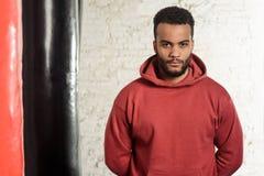 Красивый спортсмен в maroon шлямбуре стоит в спортзале Стоковые Изображения