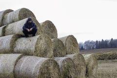 Красивый спортсмен отдыхает на стоге сена Стоковые Фотографии RF