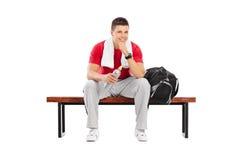 Красивый спортсмен сидя на деревянной скамье Стоковое Изображение RF