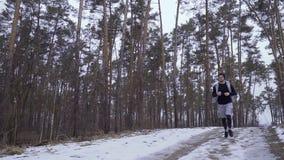 Красивый спортсмен смотрит на его наручных часах и продолжает jogging сток-видео