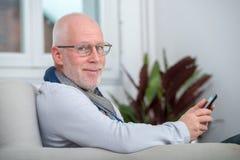 Красивый старший человек используя телефон на софе Стоковое Изображение RF