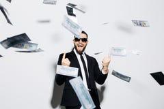 Красивый стильный бизнесмен в солнечных очках и костюм возбудили клекот указанный вверх на дождь денег мухы изолированный на бело Стоковое Фото
