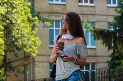 Красивый стильный кофе студента девушки выпивая на улице города Стоковое Фото