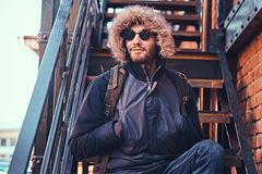Красивый стильный молодой человек сидя на лестницах снаружи стоковые изображения