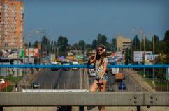 Красивый стильный студент девушки стоит на мосте автомобиля с b Стоковое Фото