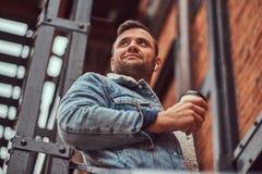 Красивый стильный человек нося куртку джинсовой ткани держа на вынос кофе на лестницах снаружи стоковое фото rf