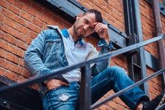 Красивый стильный человек нося куртку джинсовой ткани представляя на лестницах снаружи, смотрящ камеру стоковая фотография
